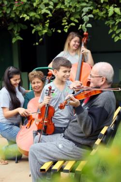 Encontro de gerações. André Xavier ensina o Sr. Guilherme Guedes a tocar violino