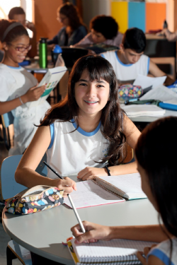 : Mariana Giroto Garcia Lopes estudando no pátio da escola entre amigos e professores